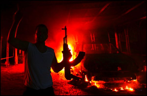 An armed man outside the burning US consulate in Benghazi, Libya