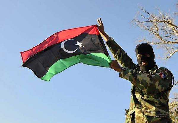 A member of the Libyan army's Thunderbolt Brigade flies the Libyan flag as the army prepares for deployment in Benghazi