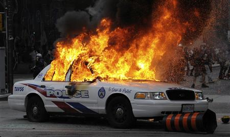 A police car set on fire by anarchist demonstrators burns in the midst of protests during the G20 summit in downtown Toronto