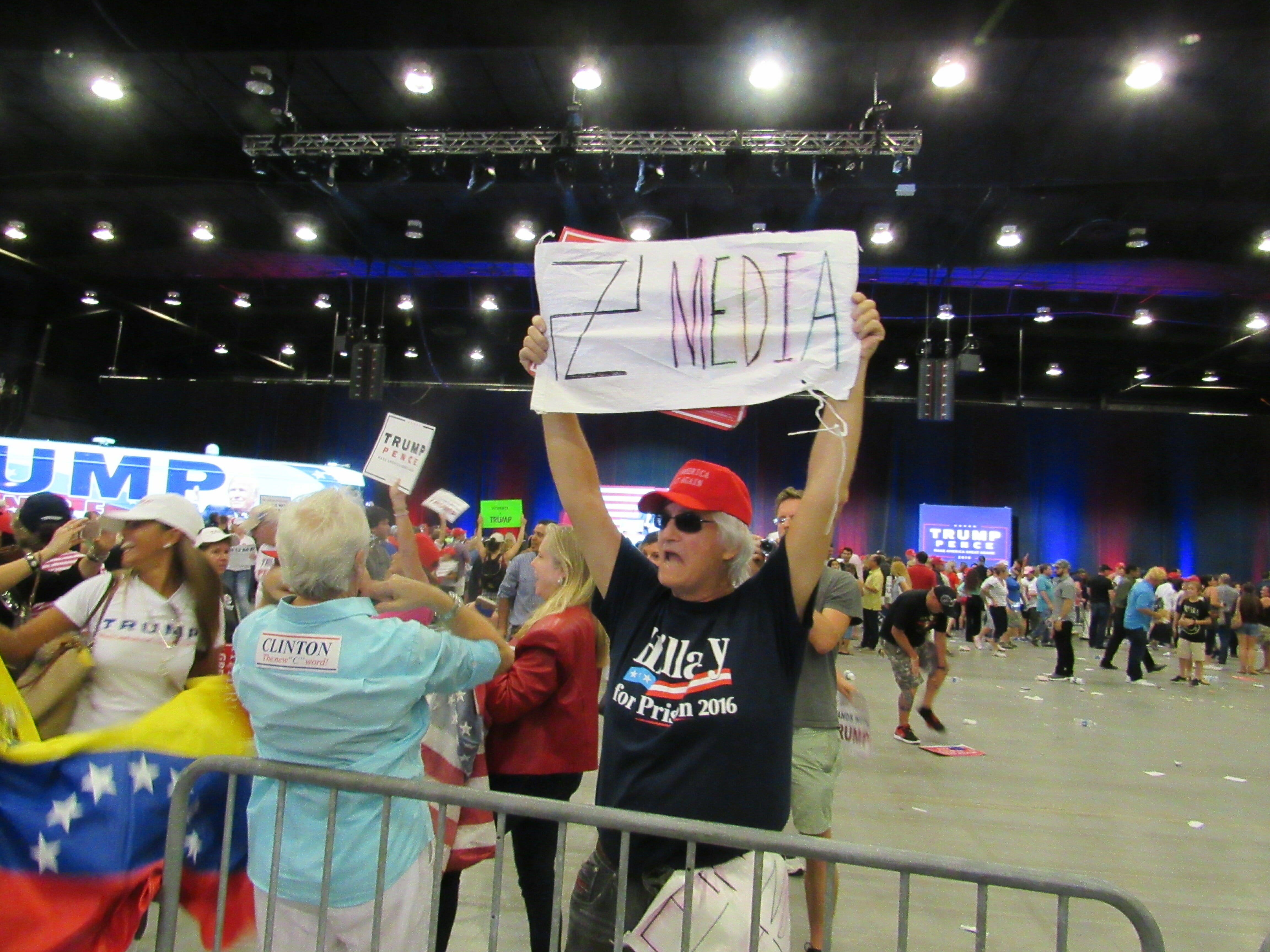 Trump supporter holds sign in front of media pen at West Palm Beach rally