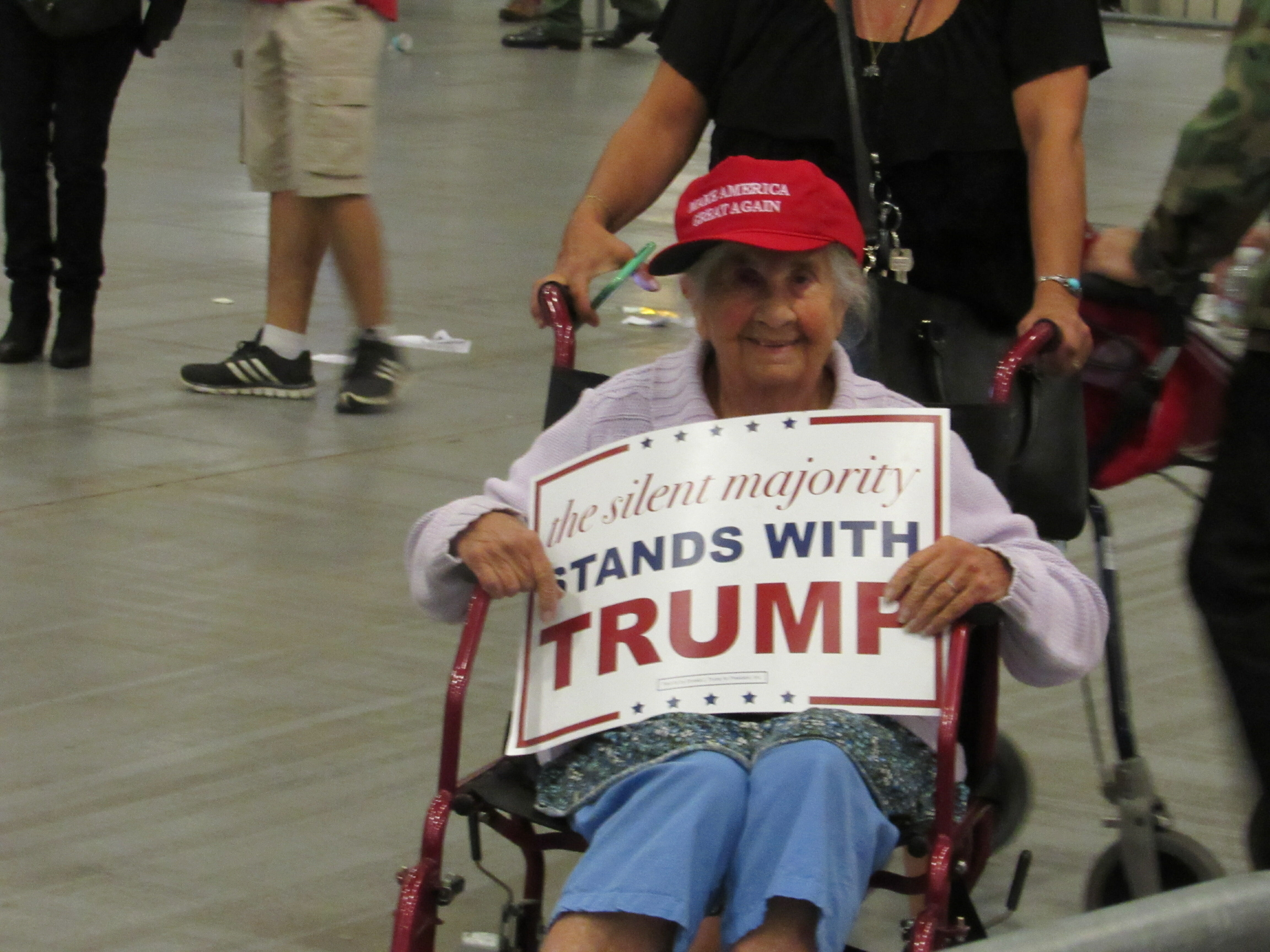 Elderly woman holds Trump sign for media after West Palm Beach rally