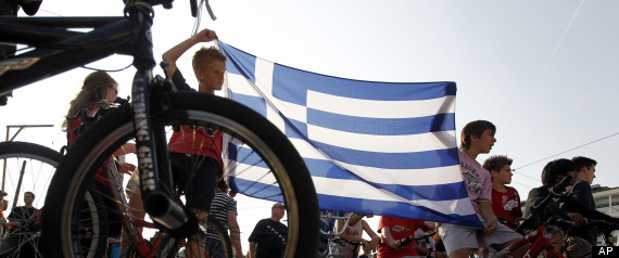 Children on bicycles hold a Greek flag as they taking part on a  peaceful rally in Athens, on Wednesday, June 1, 2011. For over a week,  Greeks have held peaceful anti-austerity protests in Athens and other cities, in a new Internet-sparked movement that most commentators applaud. (AP Photo/Petros Giannakouris)