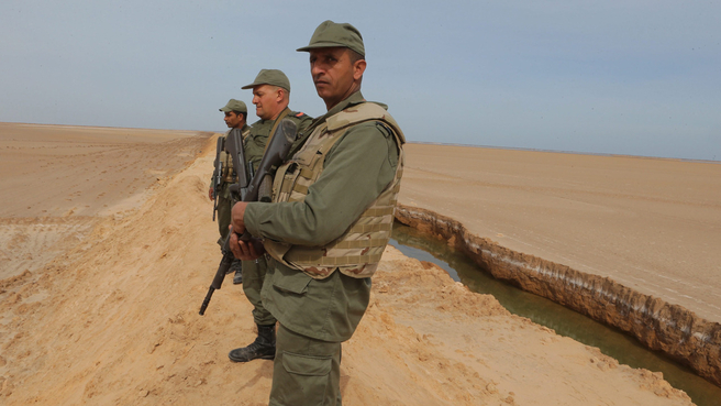 epa05147097 Tunisian soldiers stand on a sandbank during a presentation of the anti-jihadi fence, near Ben Guerdane, eastern Tunisia, close to the border with Libya, 06 February 2016. Tunisian Defense Minister Farhat Horchani inspected the first completed part of the 196-kilometer ditch, which aims to render the entire border impassable by vehicles.  EPA/MOHAMED MESSARA